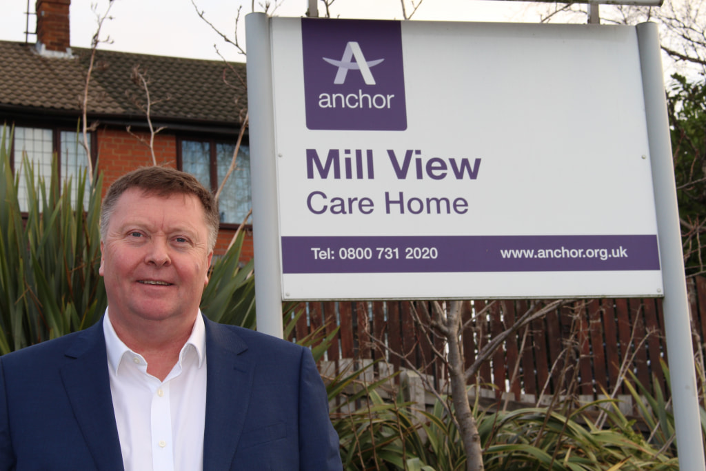 Managing Director Mark Greaves by Mill View sign