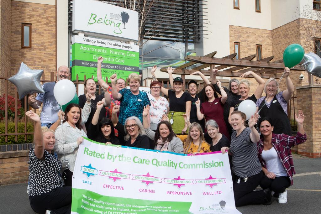 Belong Wigan team with CQC outstanding banner