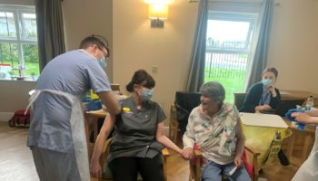 Ebor Court Care Assistant Marie and resident Ann hold hands as they receive the Covid-19 vaccination together