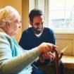 Male nurse showing a digital tablet to an elderly woman
