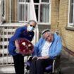 Lorraine receiving flowers from resident Margaret