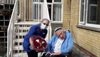 Lorraine receiving flowers from resident Margaret